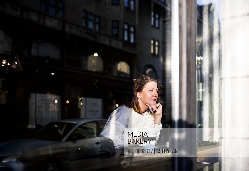 Smiling woman looking through window while sitting in cafe