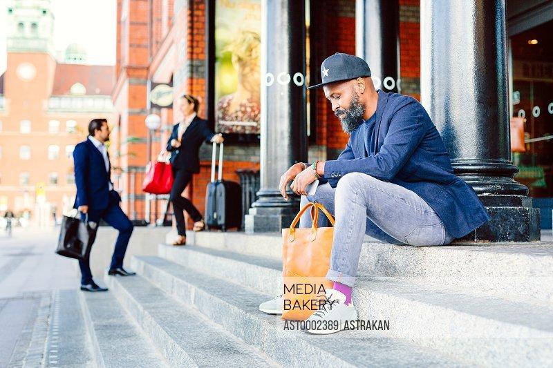 Businessman sitting on steps outside railroad station