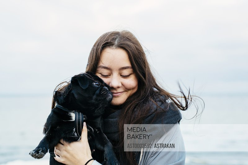 Happy young woman carrying dog on beach against sky