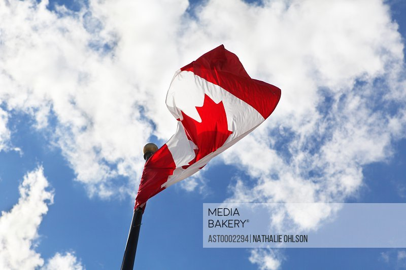 Low angle view of Canadian flag swaying against cloudy sky