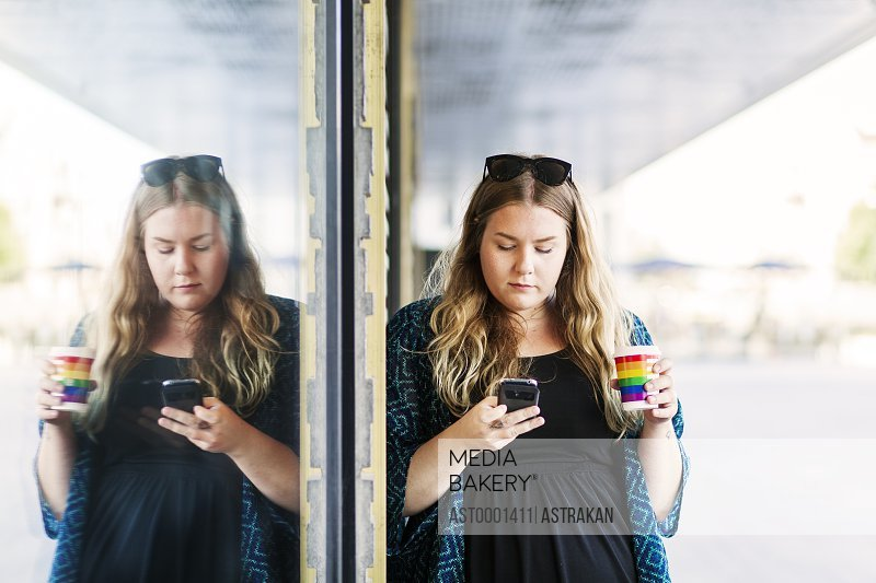 Young woman using mobile phone while holding coffee cup