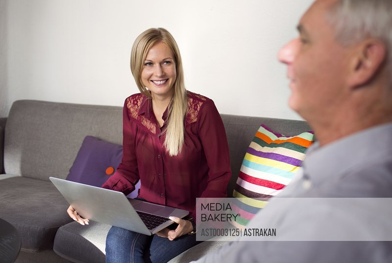 Business woman holding laptop while discussing with colleague in restaurant