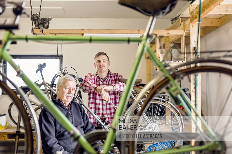 Portrait of confident father and son in bicycle shop