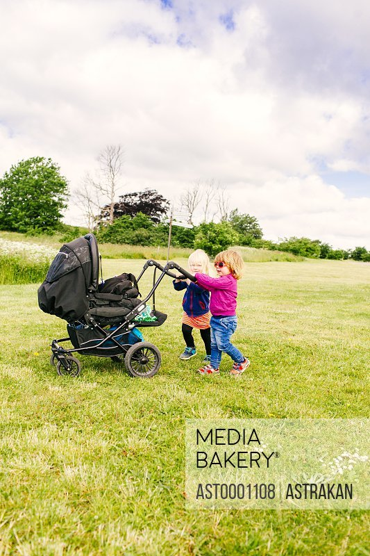 Girls playing with baby carriage on grassy field against cloudy sky