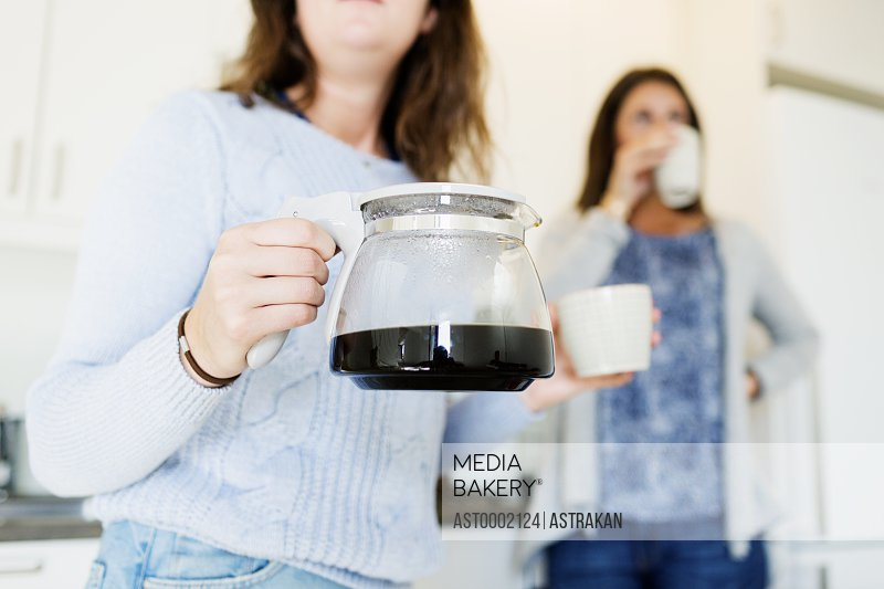 Midsection of woman holding kettle while friend drinking coffee in new home