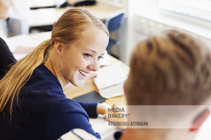 High angle view of smiling young woman with classmate at desk in classroom