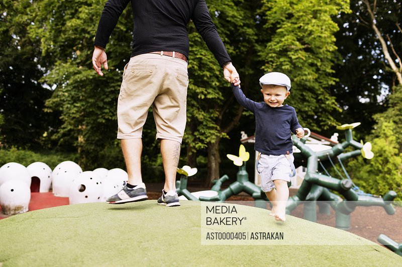 Father and son playing on artificial hill in playground
