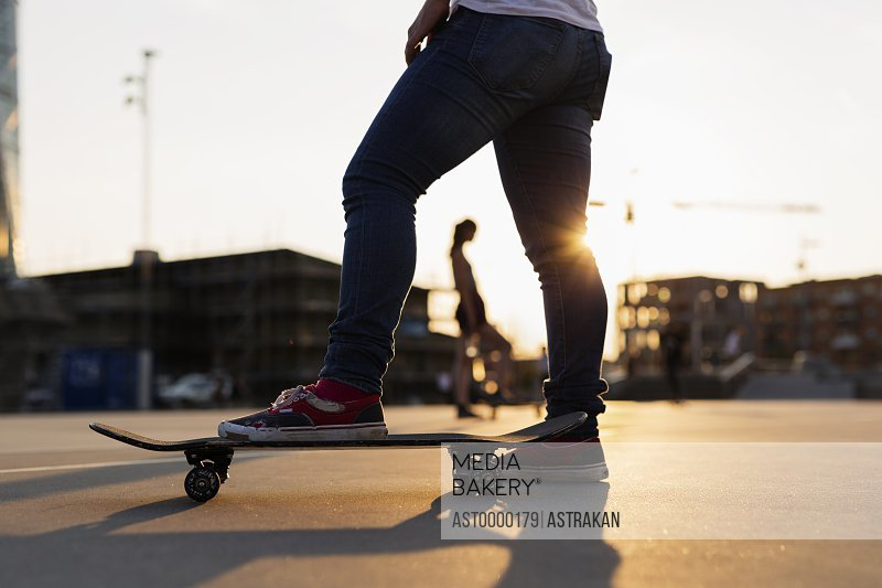 Low section of teenage girl skateboarding in skatepark during sunset