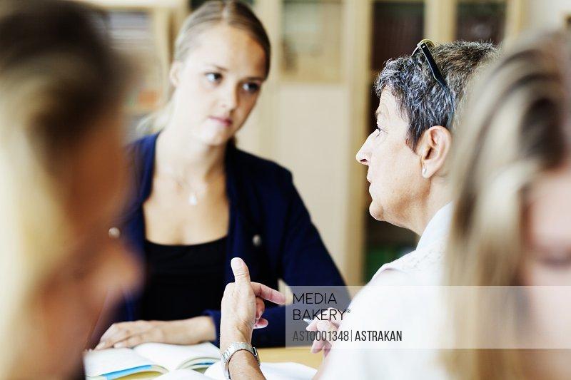 Female teacher explaining to student in classroom