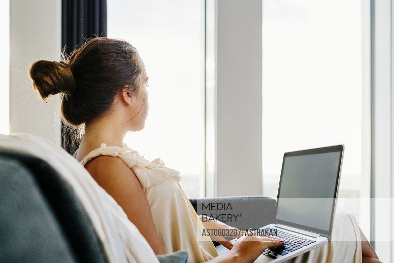 Businesswoman using laptop while sitting on sofa at hotel room