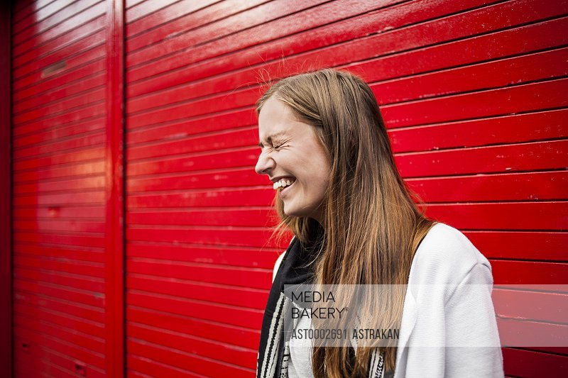 Cheerful woman with eyes closed standing against red shutter