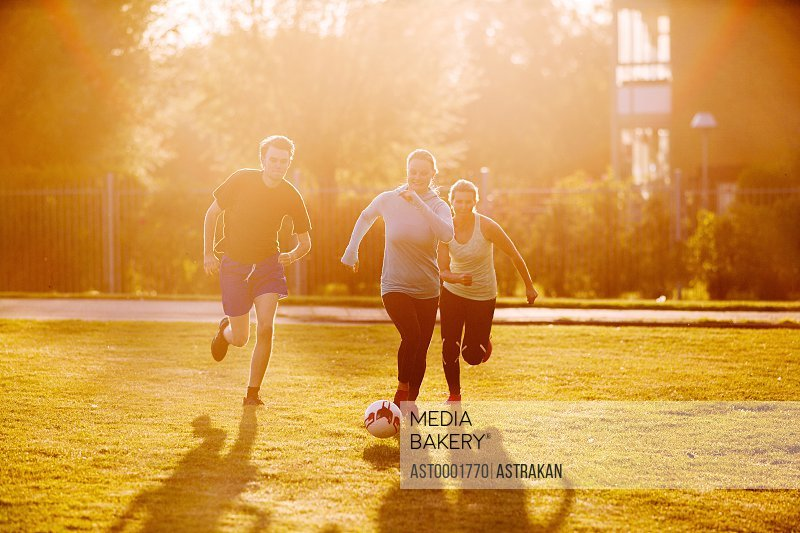 Young man playing soccer with female friends at park during sunset