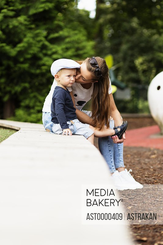 Young woman kissing while assisting son in wearing sandal at park