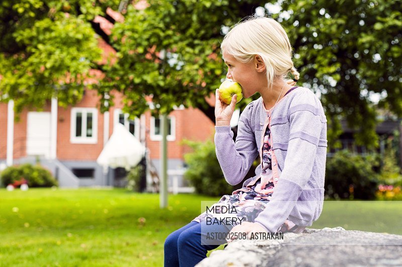 Side view of girl eating apple in yard