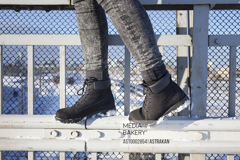 Low section of woman walking on metal gate during winter
