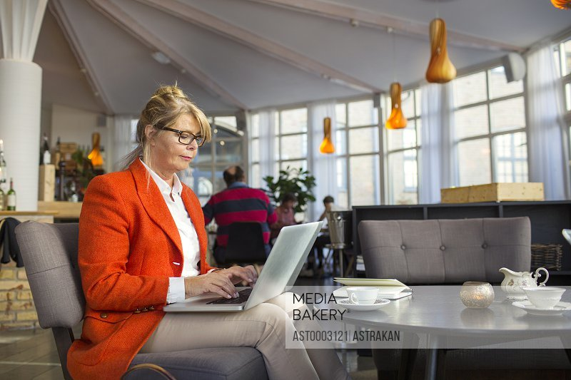 Businesswoman using laptop while sitting in restaurant