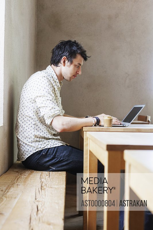 Side view of businessman using laptop in cafe
