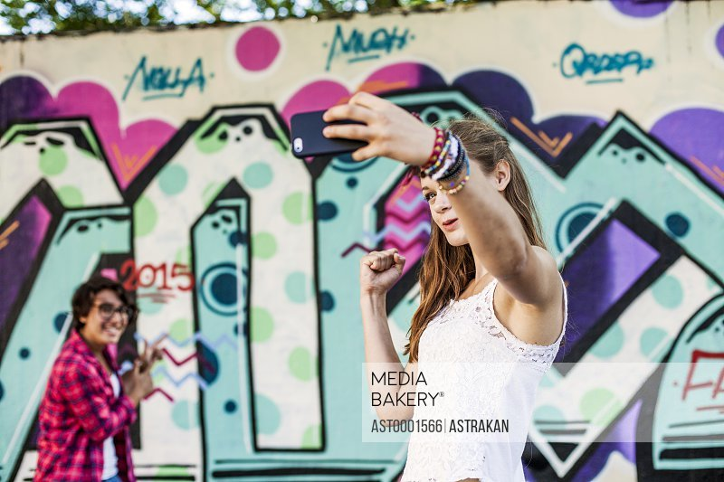 Girls taking selfie and gesturing while standing against wall with graffiti