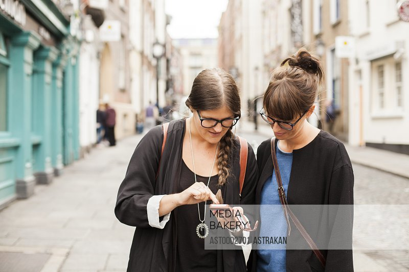 Female friends using smart phone on city street