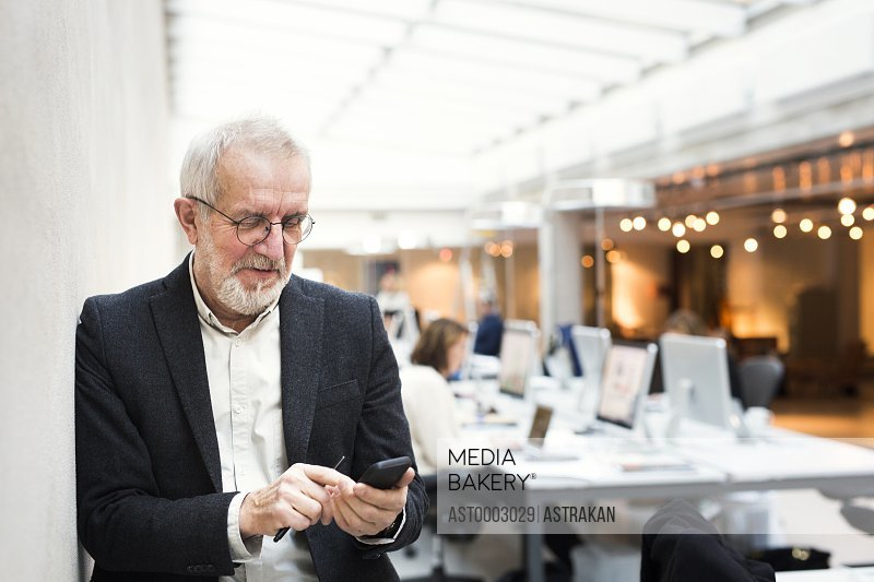 Senior businessman using mobile phone while leaning on wall in office