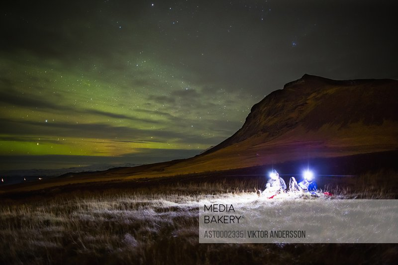 People with illuminated lighting equipments sitting on grassy field against mountain at night