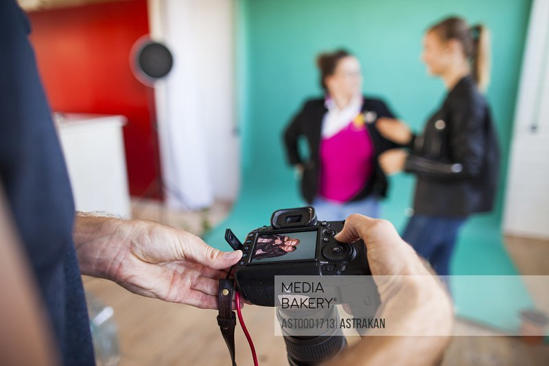 Cropped image of photographer checking photographs on camera while models discussing in background at studio