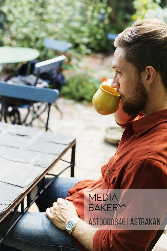 Man drinking coffee while sitting by table at greenhouse