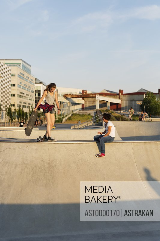 Female skateboarders at the edge of ramp in skate park