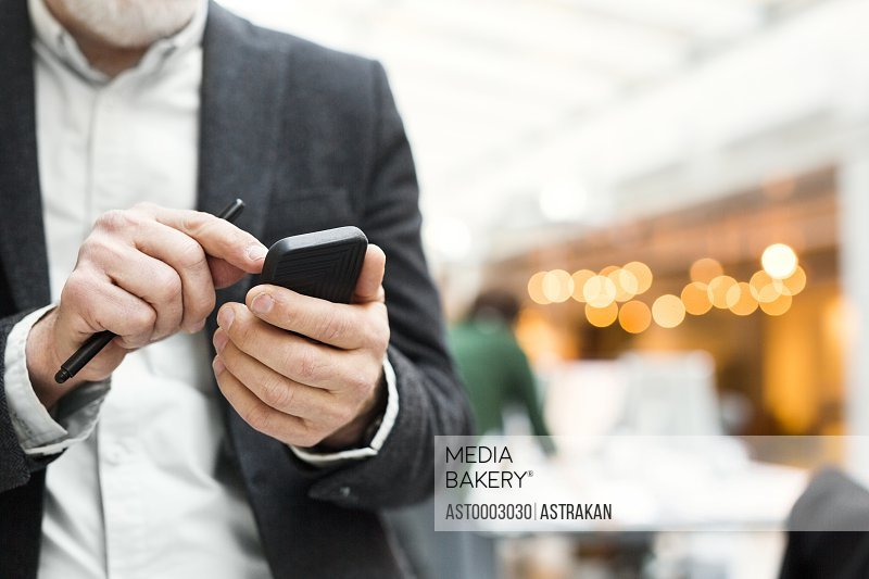 Midsection of senior businessman using mobile phone in office