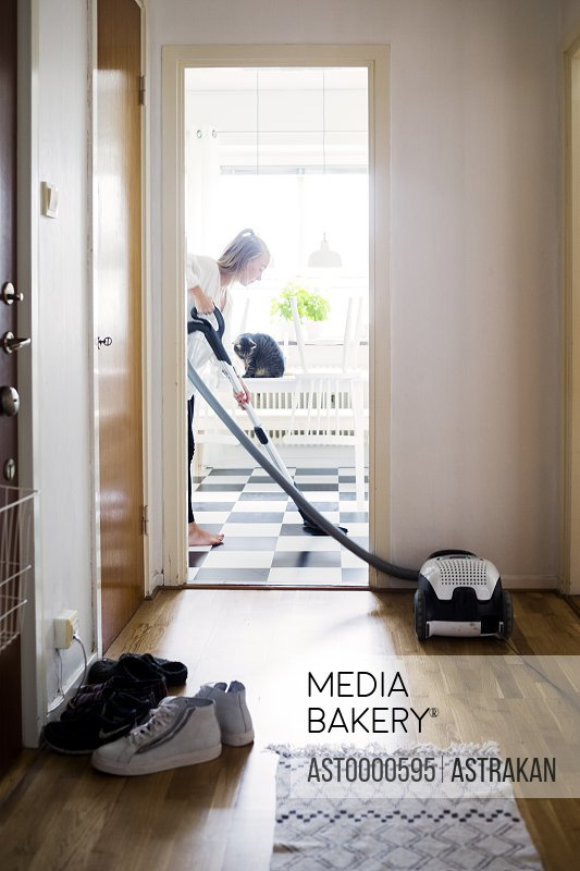 Woman cleaning using vacuum cleaner to clean floor at home