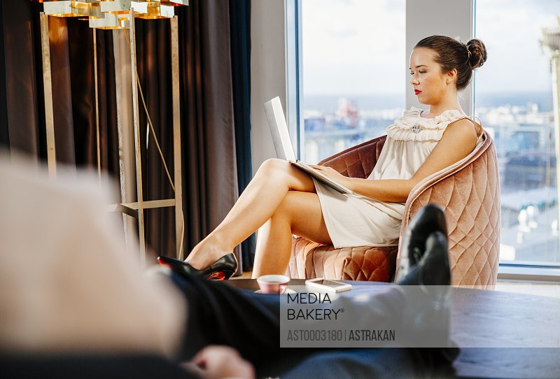 Man resting while businesswoman using laptop in hotel room