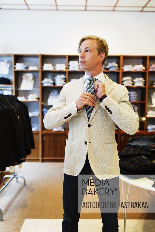 Handsome customer adjusting tie in clothing showroom
