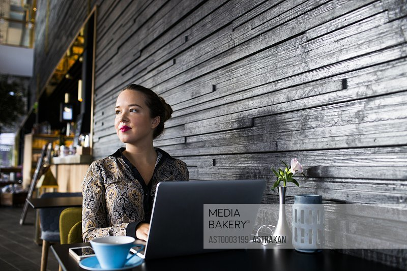 Beautiful businesswoman using laptop while sitting at table