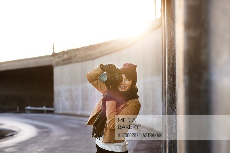 Woman photographing with camera on street