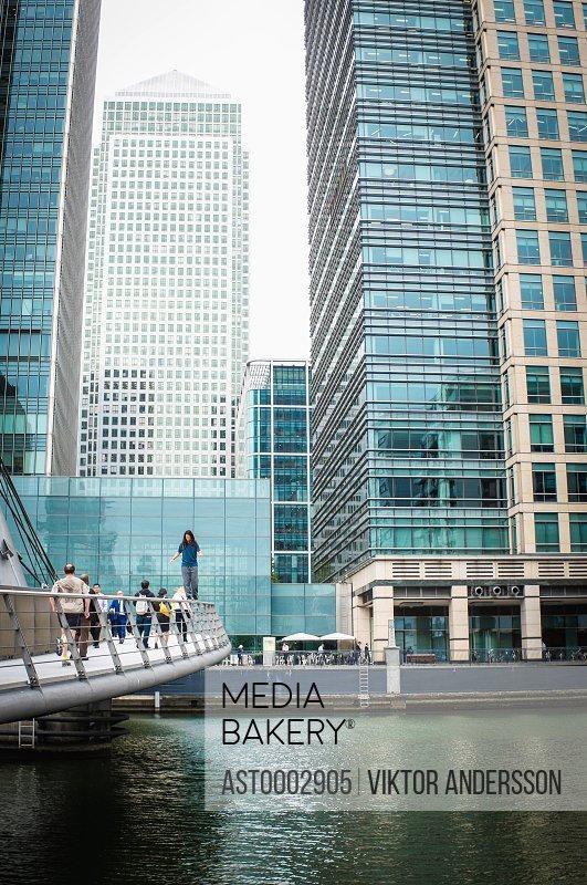 Woman walking on railing of footbridge over river against modern buildings