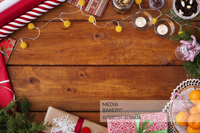 Directly above shot of Christmas decorations and gifts on wooden table