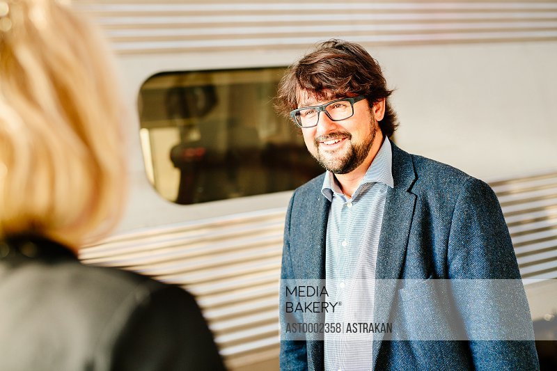 Happy businessman looking at female colleague on railroad station