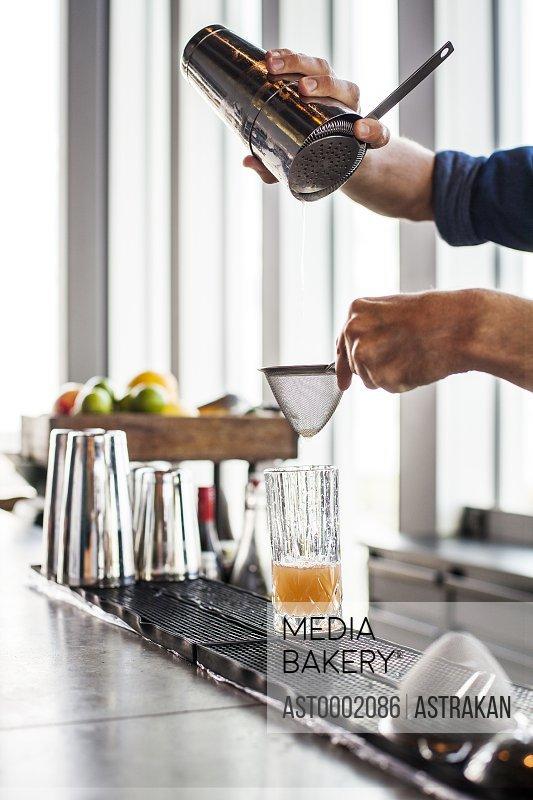 Cropped image of bartender making cocktail at bar