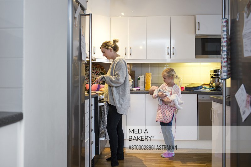 Girl carrying baby while mother preparing pancake in kitchen