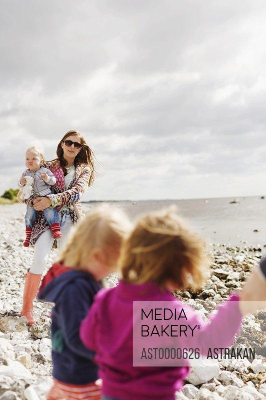 Family at beach on sunny day against cloudy sky