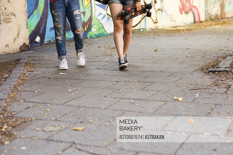 Low section of girls holding skateboards walking on footpath