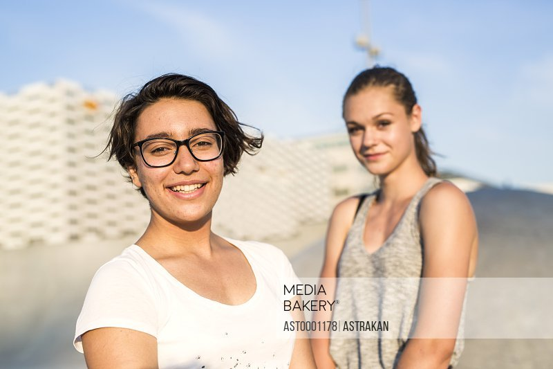 Portrait of smiling teenage girl with female friend at skate park