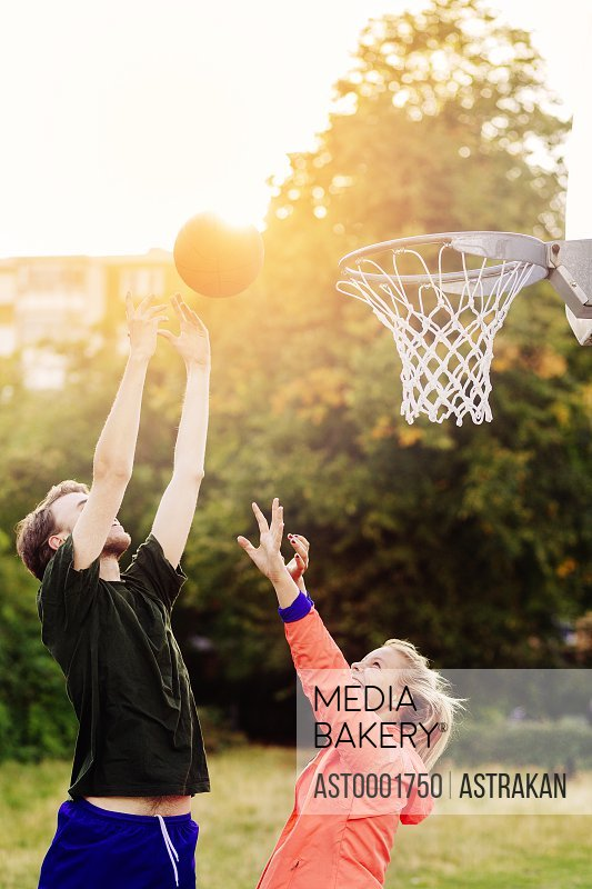 Friends playing basketball at park during sunset