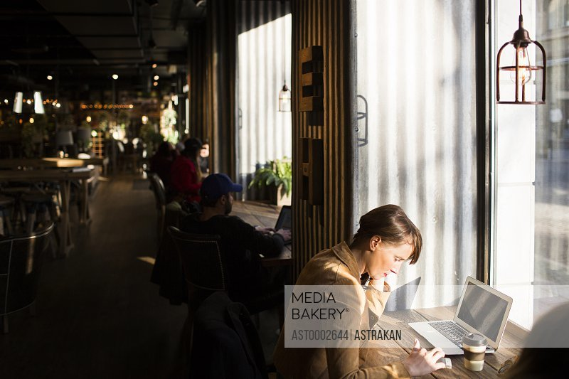 Woman using smart phone while sitting at cafe table