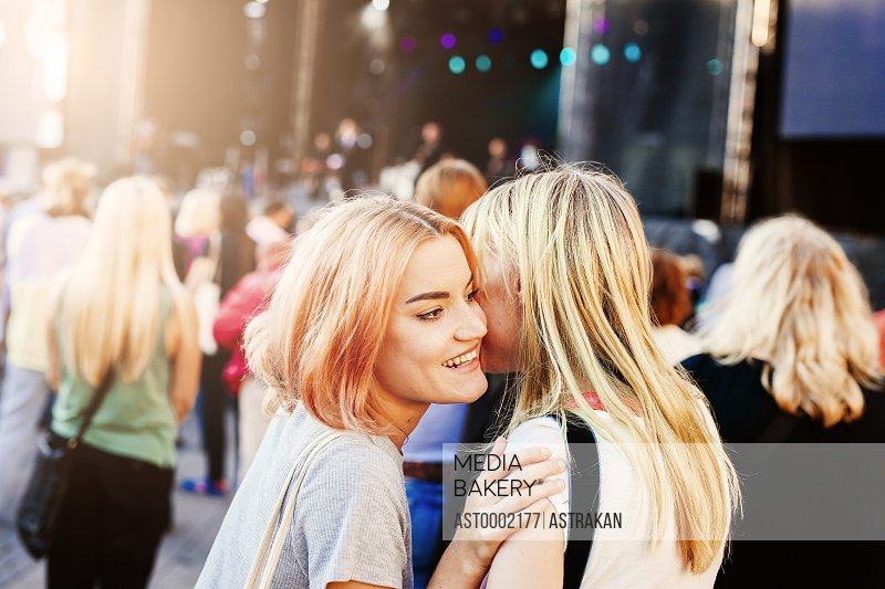 Young woman whispering into friend's ear