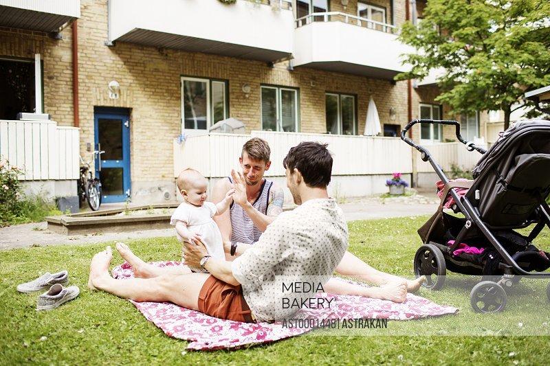 Gay men playing with baby girl at yard