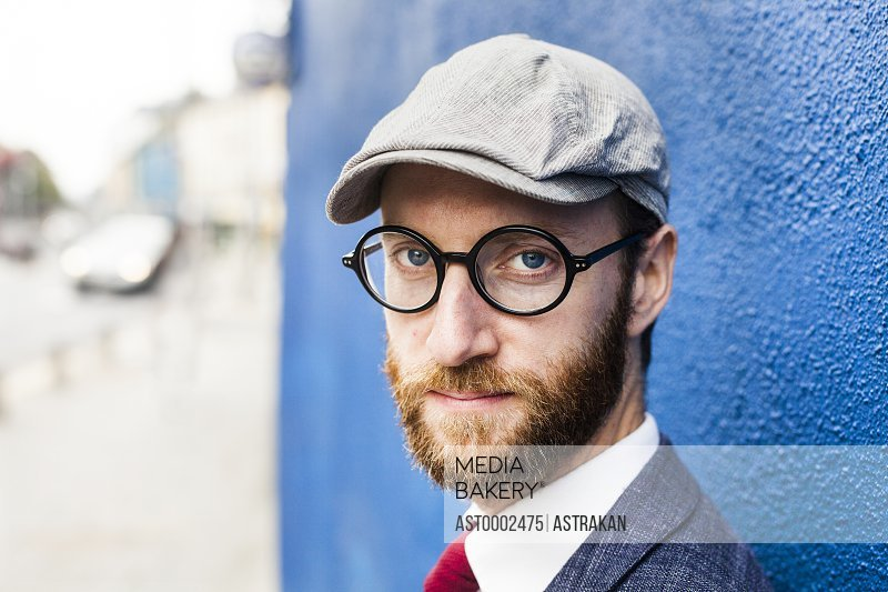 Portrait of confident man by blue wall