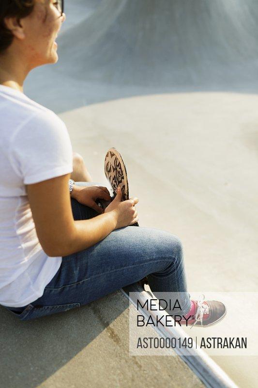 Side view of teenage girl sitting at edge of skateboard ramp