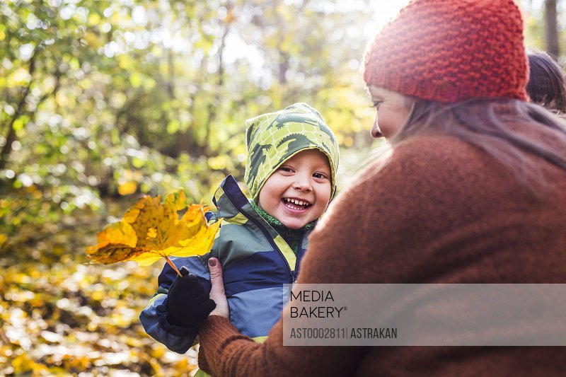 Mother with happy boy holding leaf in forest during autumn