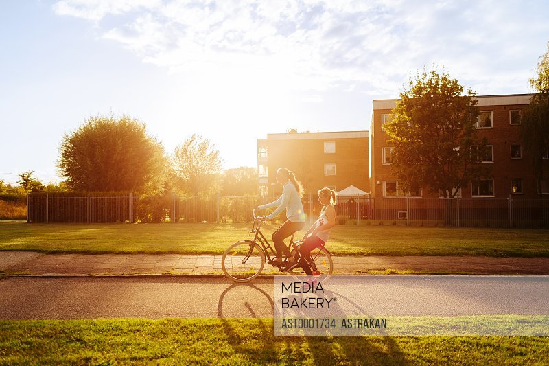 Side view of sporty women riding bicycle on street during sunset
